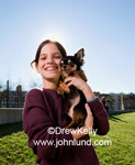 Young hispanic girl happily holding her Chihuahua next to her faces . Green grass, blue cloudless sky, smiling girl.